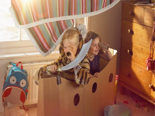 Two children playing pirates in a cardboard box ship